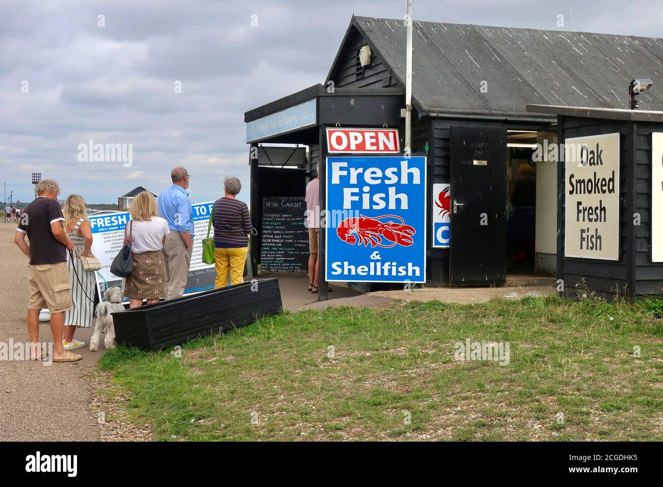 Aldeburgh, Suffolk, UK - 9 September 2020: Sunny autumn day on the East Anglia coast. People in a queue at a fresh fish and seafood seller shed. Stock Photo