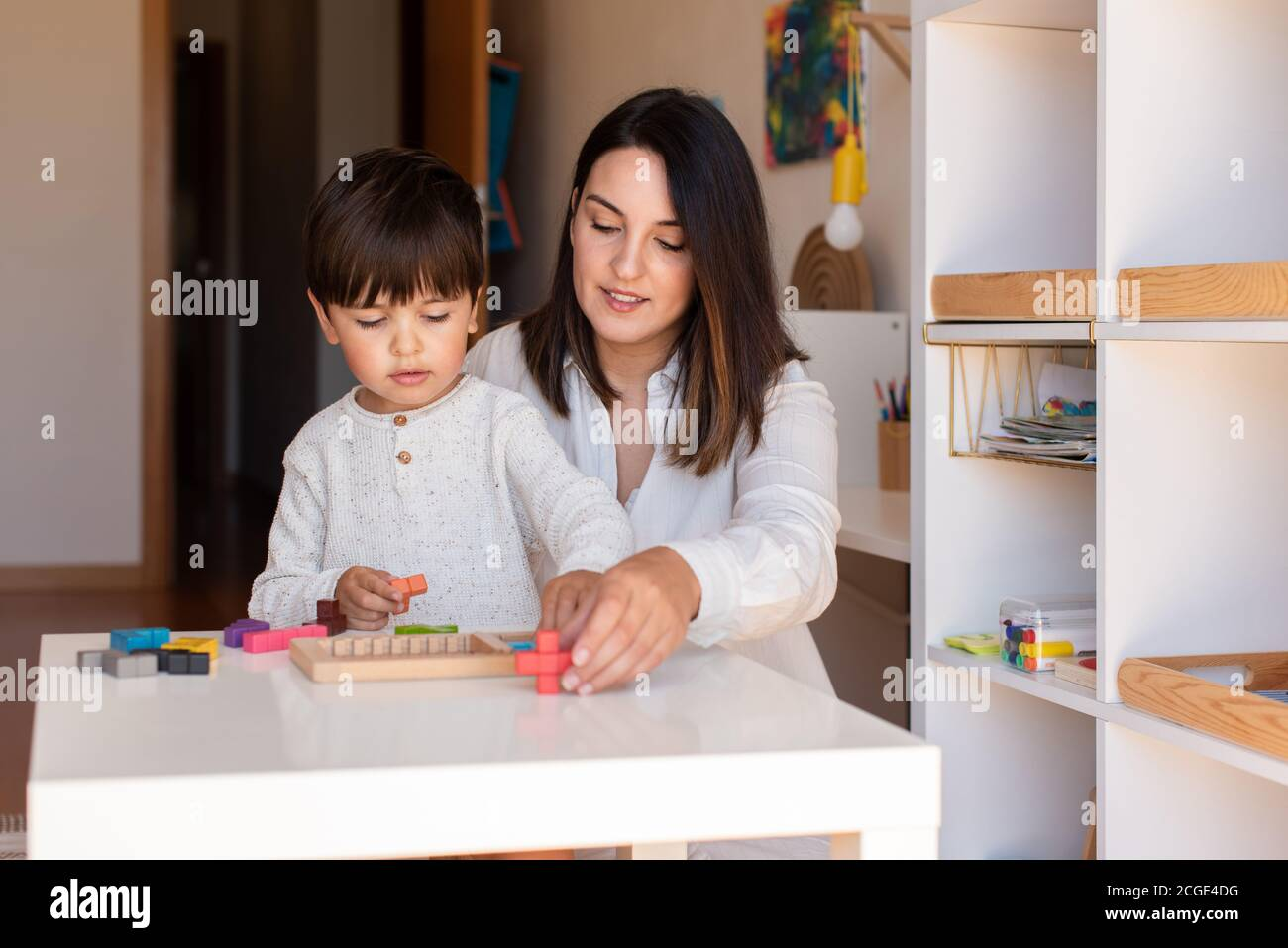 Lillte Kid playing with a tetris wood puzzle and mother or teacher help. Homeshooling. Learning Community. Montessori School Stock Photo