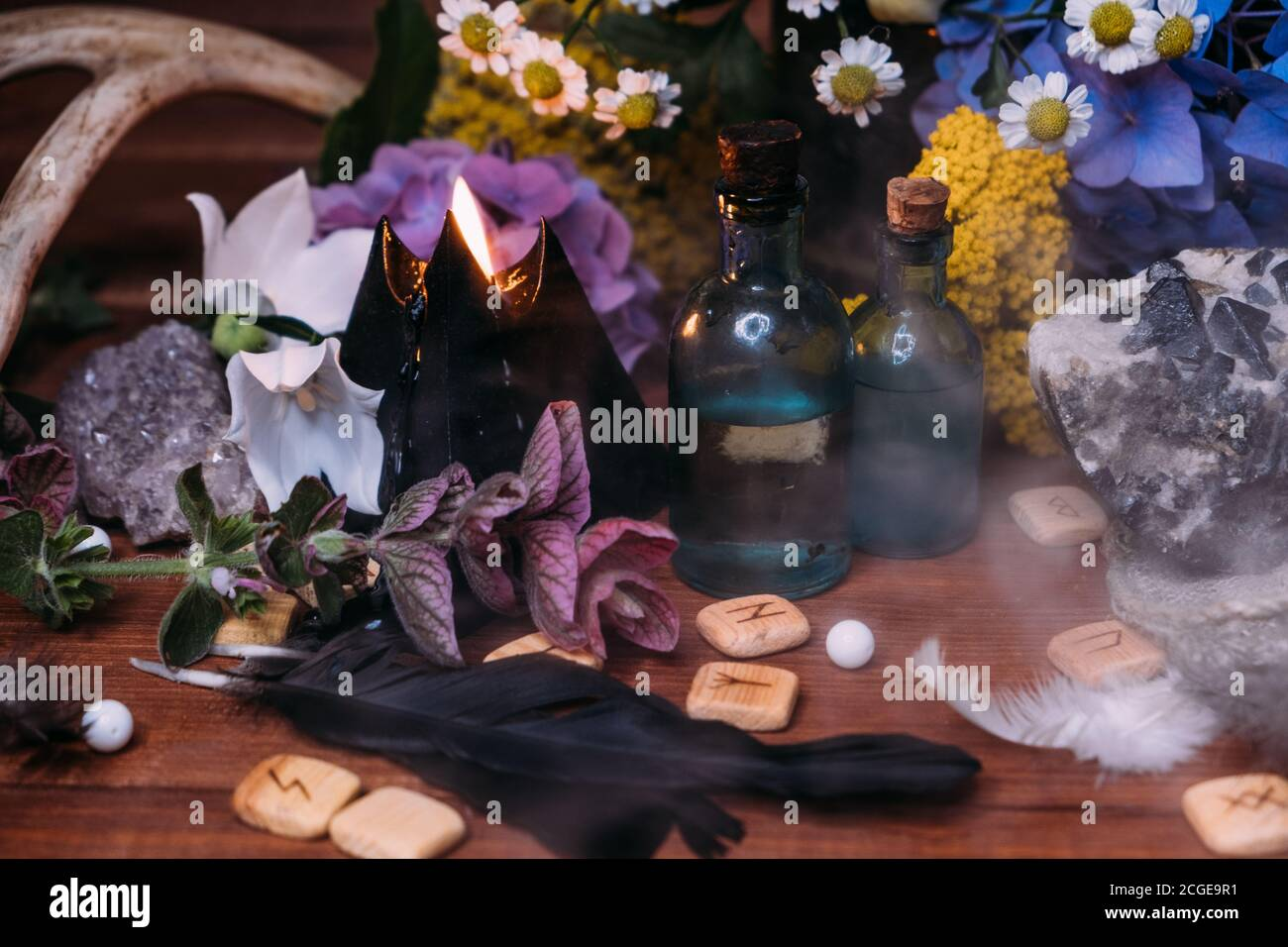 Magic potion bottle. Witchcraft halloween concept with potions, herbs and occult equipment. Magical still life with copy space on a dark background. Stock Photo