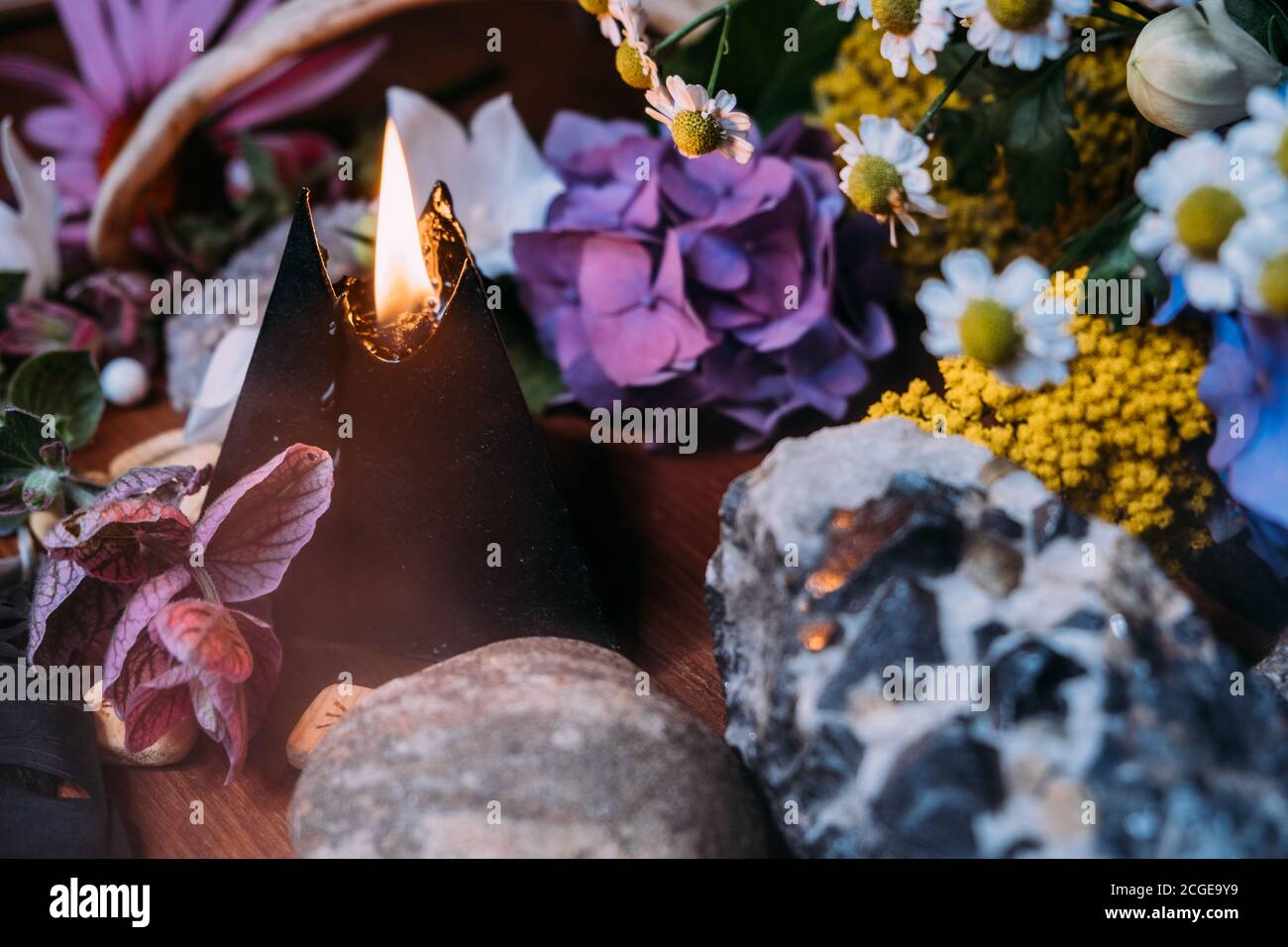 Still life with burning black candle, stones and herbs background. Black magic ritual with occult, evil and esoteric symbols. Halloween or divination Stock Photo