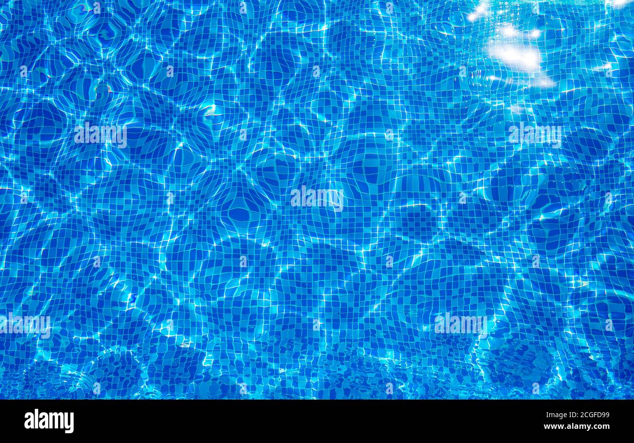 Background texture surface of blue swimming pool of water with refractive sun Stock Photo