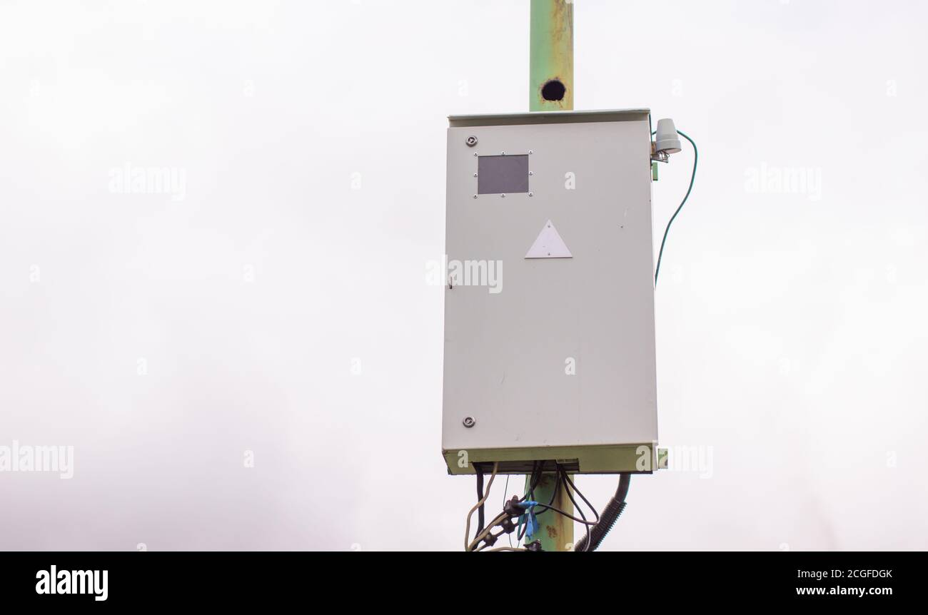 White electric box on a pole outside the house. Stock Photo