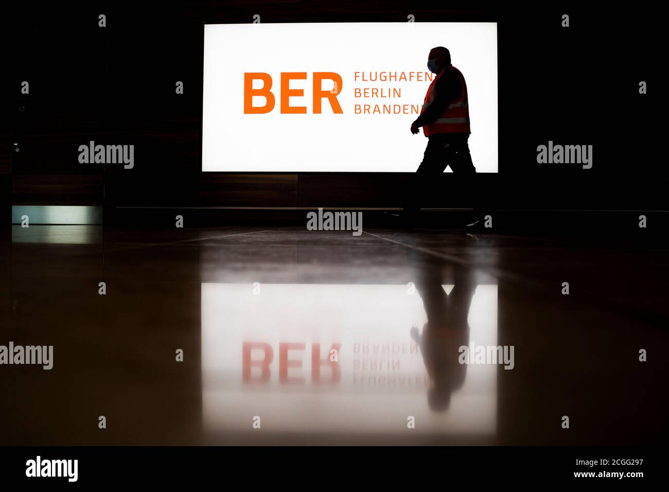 """08 September 2020, Brandenburg, Schönefeld: A man walks """"Willy Brandt"""" (BER) in front of an illuminated banner with the BER logo during a tour of the capital airport Berlin Brandenburg. The Capital Airport is scheduled to open on 31 October 2020. Photo: Christoph Soeder/dpa Stock Photo"""