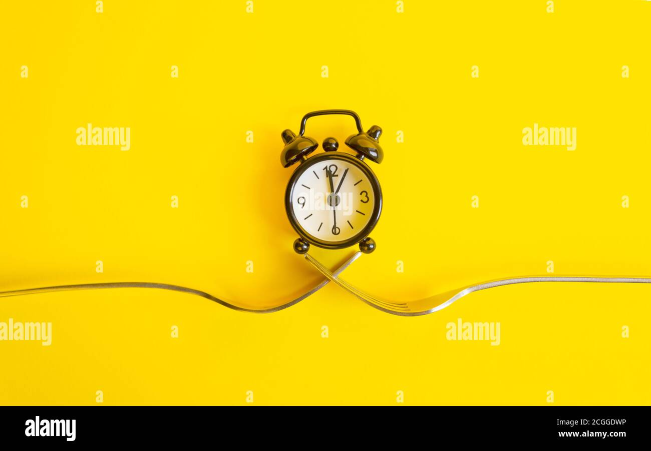 Black clock on a yellow background. Alarm clock on two forks, trend concept time . Stock Photo