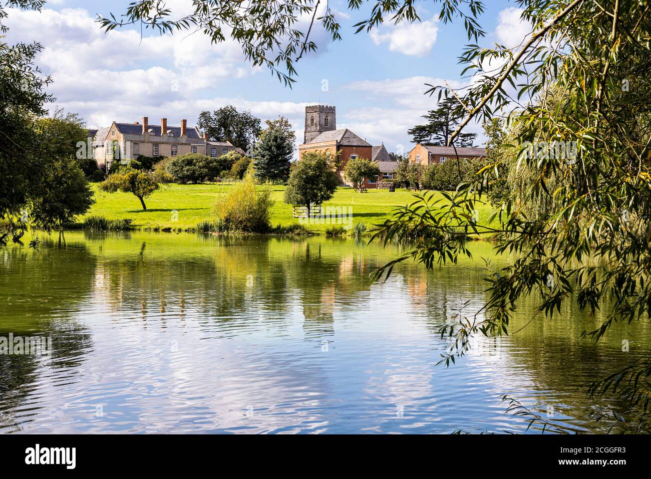 Maisemore Court and St Giles church viewed across the lake in the Severn Vale village of Maisemore, Gloucestershire UK Stock Photo