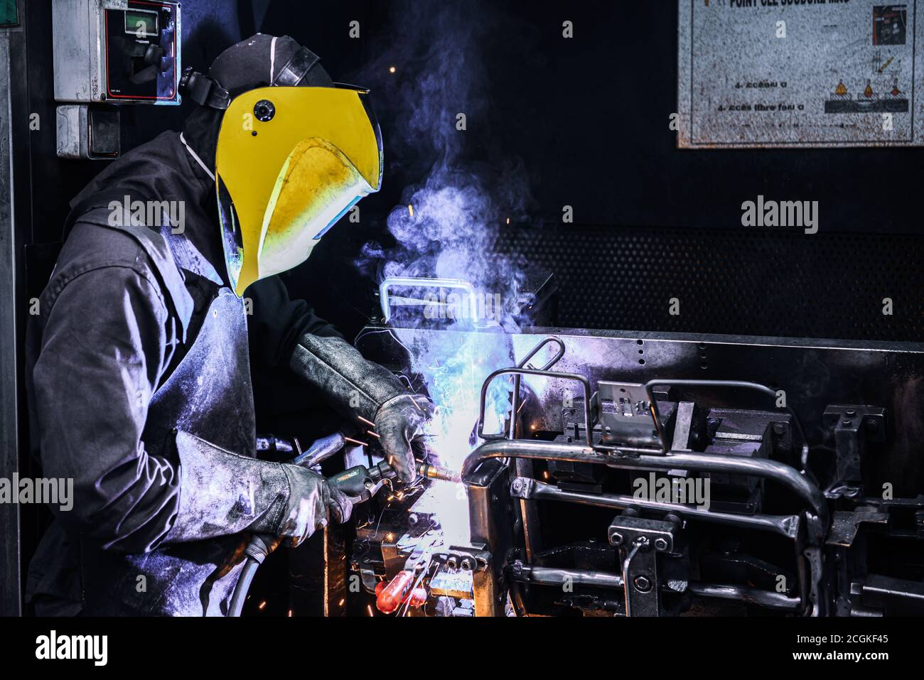 Man Welding on Assembly Line in Automotive Factory . Stock Photo