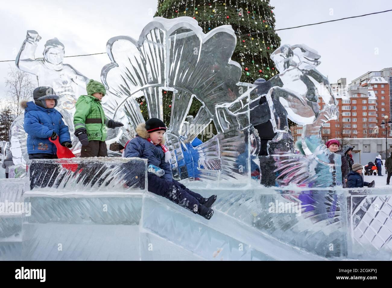 Children ride with an ice slide on the background Christmas tree in the center Krasnoyarsk city during the winter New Year holidays. Krasnoyarsk Terri Stock Photo