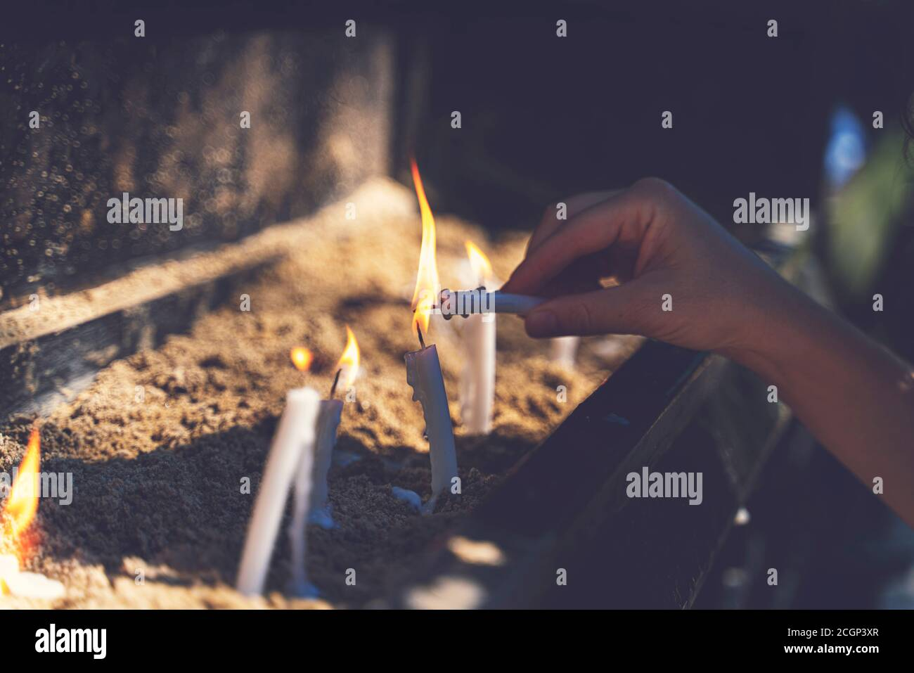 Woman praying and burning candles in the garden of the Virgin Mary house. Burning white candles on stand. Worship Stock Photo