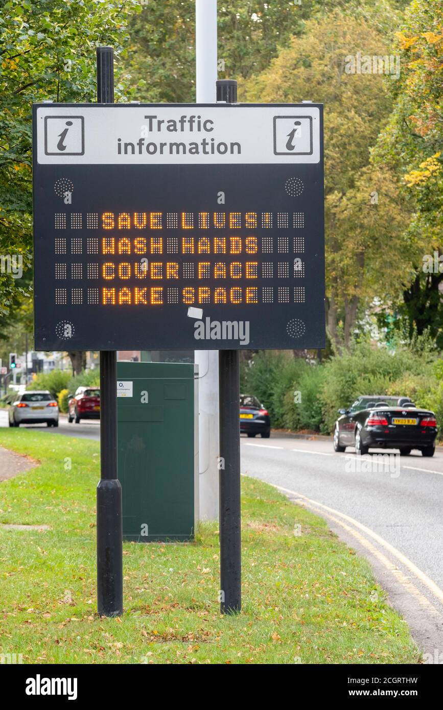 COVID-19 slogan message on traffic information matrix sign. Save lives, wash hands, cover face, make space. Cars on road to Southend on Sea, Essex, UK Stock Photo