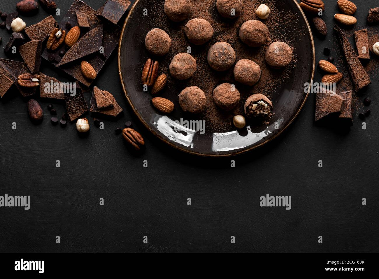 Chocolate truffles with dark chocolate and nuts on black background, top view, copy space. Vegan homemade chocolate energy balls or truffles for desse Stock Photo