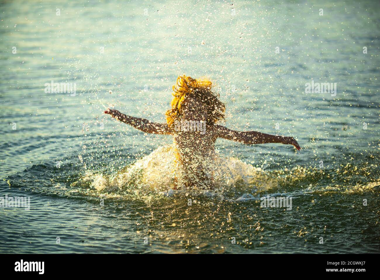 Blurred motion silhouette of happy kid playing in the sea. Child having fun on ocean outdoors. Summer vacation and healthy lifestyle concept. Stock Photo