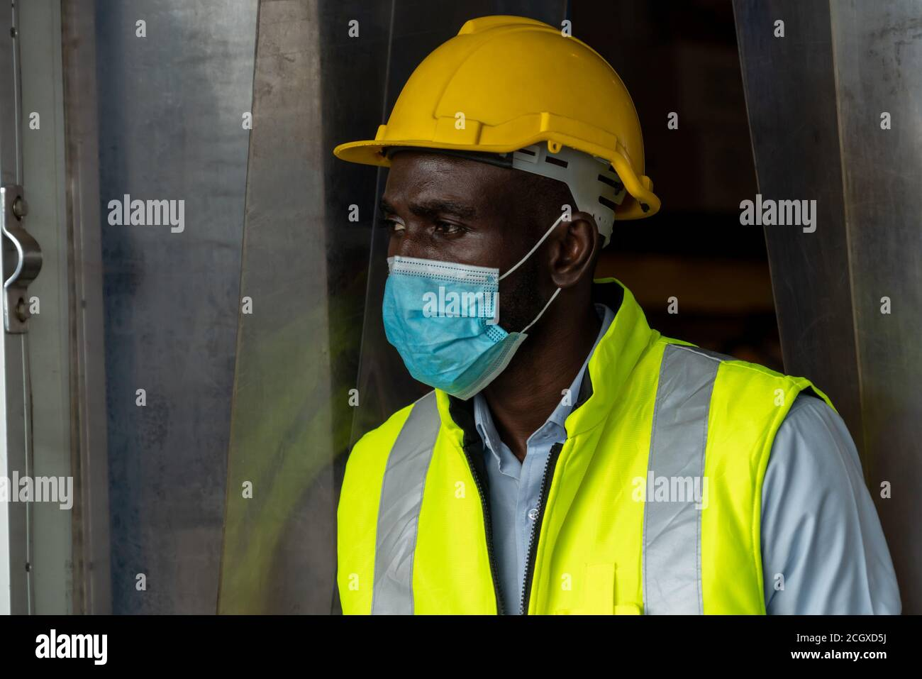 Factory industry worker working with face mask to prevent Covid-19 Coronavirus spreading during job reopening period . Stock Photo
