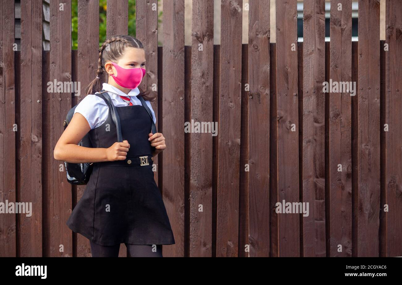 A 10 year old schoolgirl wearing a school uniform and pink face mask and looking away. Stock Photo