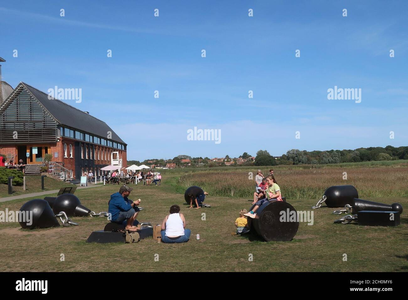 Snape, Suffolk, UK - 13 September 2020: Sunny Sunday autumn afternoon by the River Alde at Snape Maltings. Picnic on the art - To give light by Ryan Gander (2018). Stock Photo