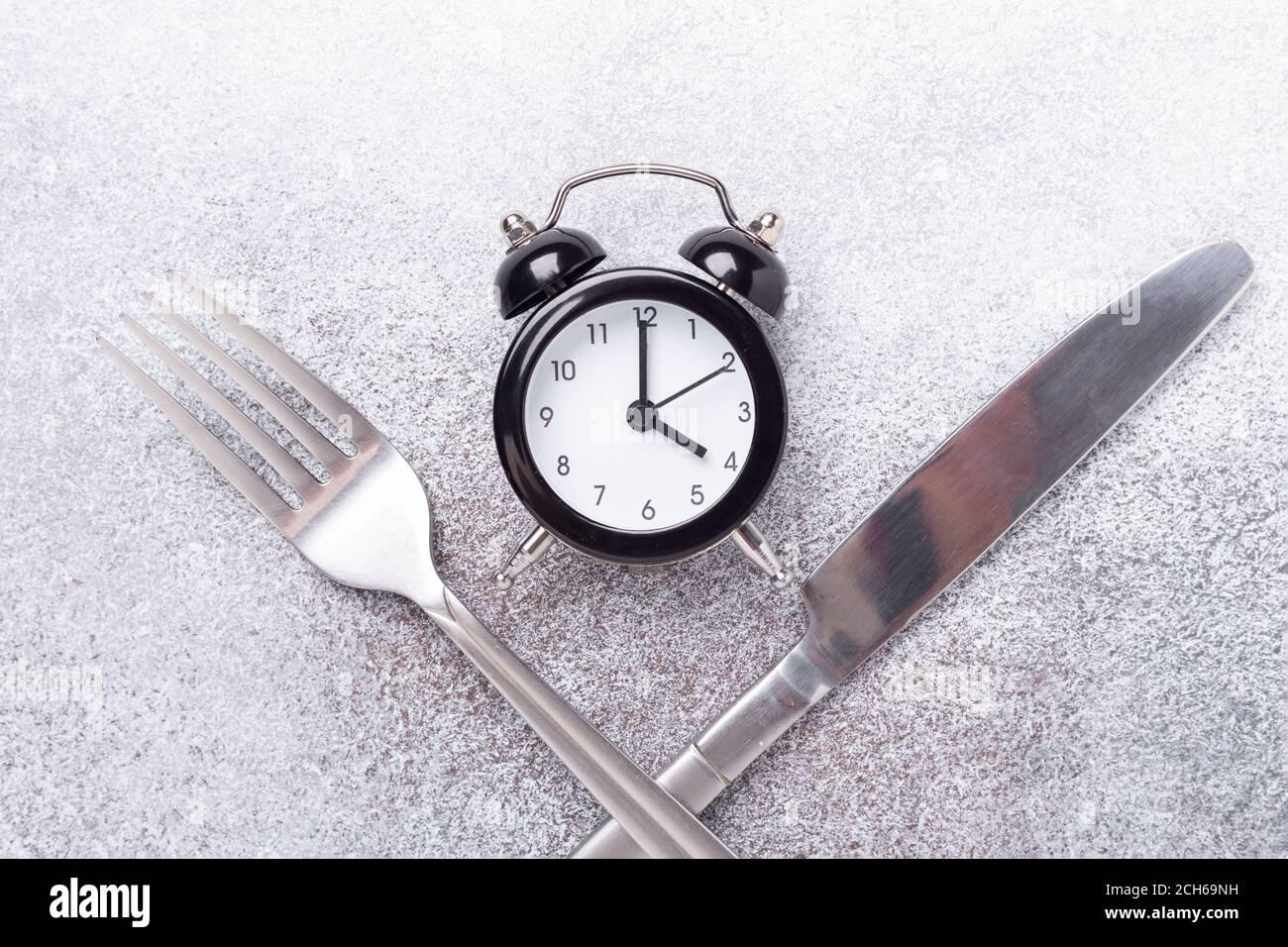 Black alarm clock, fork, knife on dark background. Intermittent fasting concept - Image Stock Photo