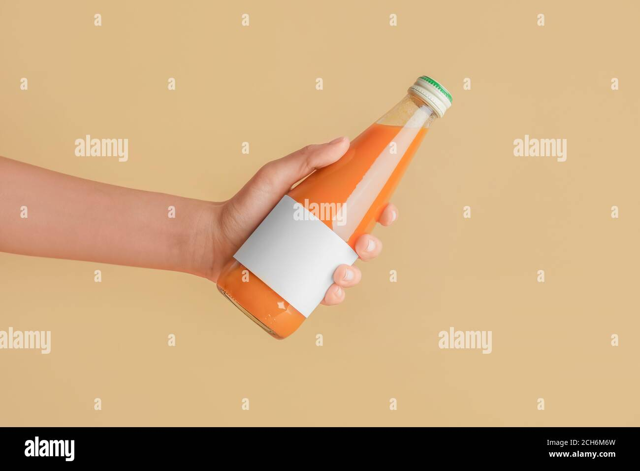 Female hand with bottle of juice on color background Stock Photo