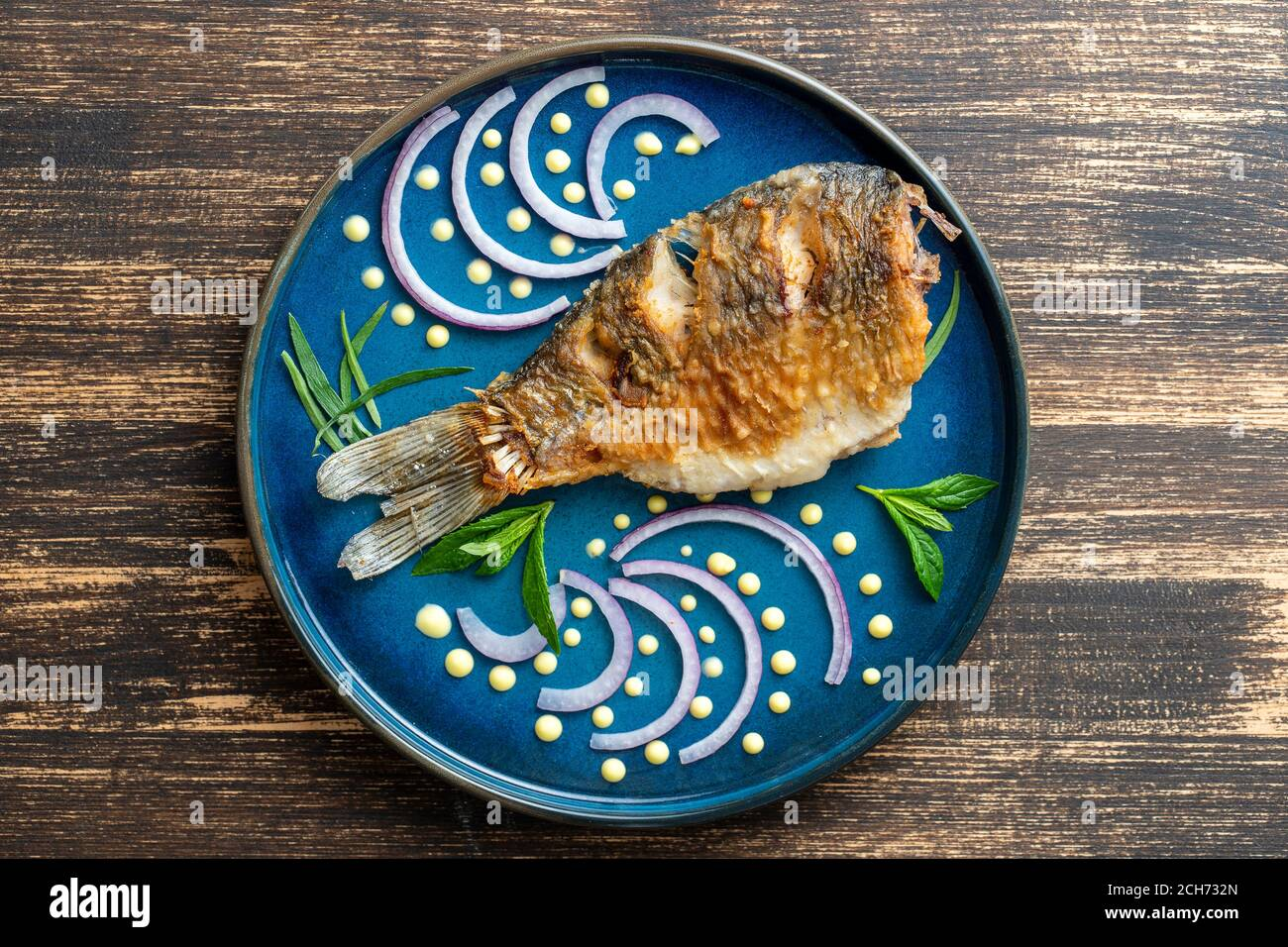 Fried Crucian Carp With Onion And Sauce Dot Painting On A Plate On A Wooden Background Top View Close Up Stock Photo Alamy