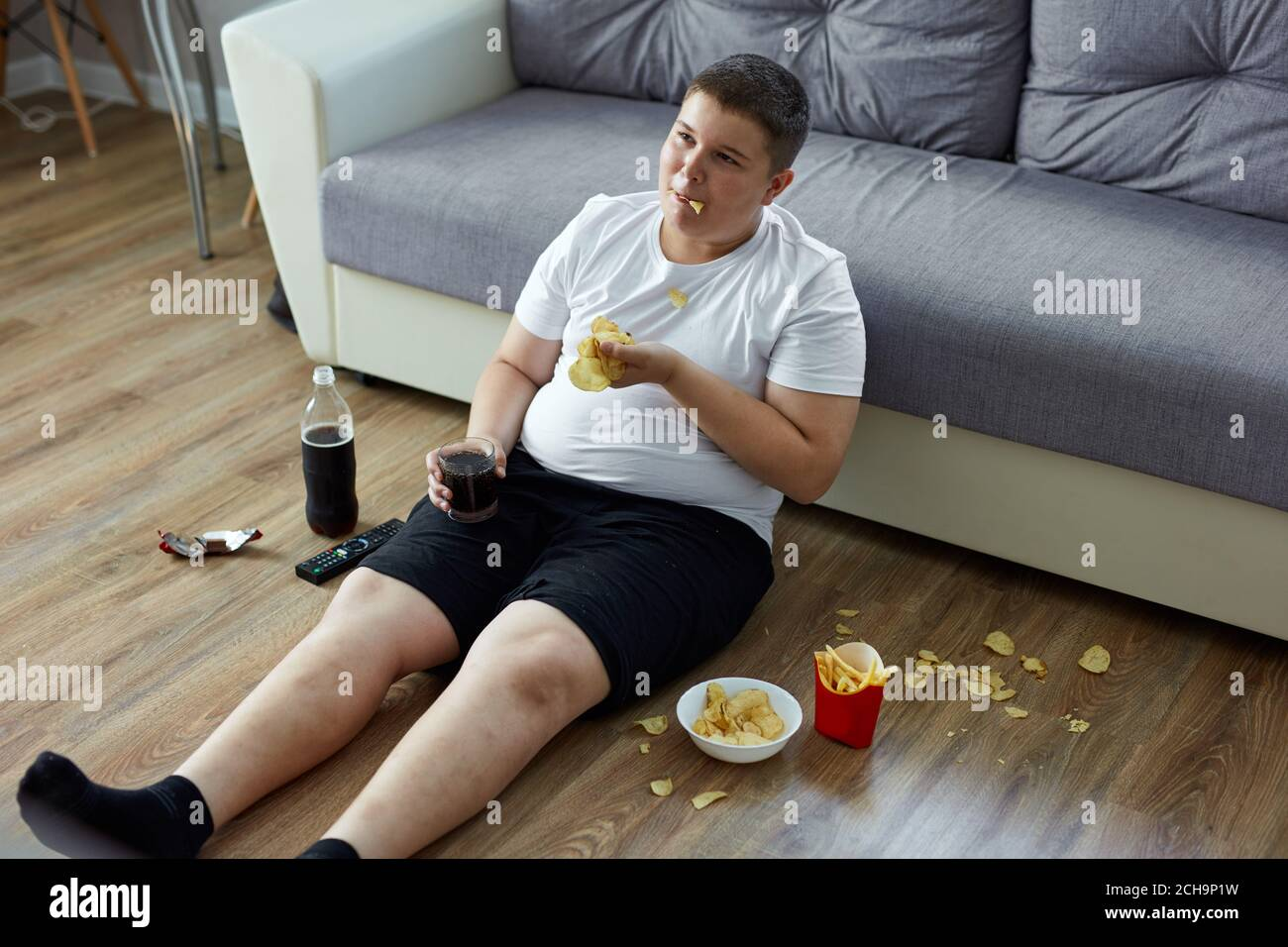 An Overweight Child Boy Enjoy Leading Unhealthy Passive Lifestyle Sits On The Floor Watching Tv And Eating He Moves A Little That Is Why He Is Fat Stock Photo Alamy