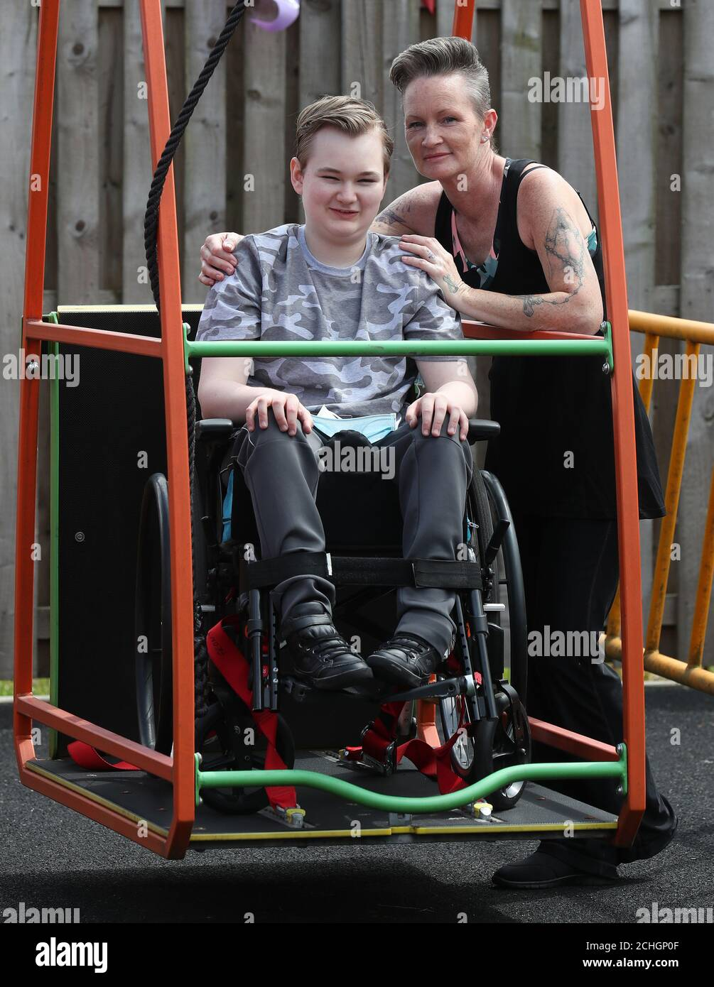 Embargoed to 0001 Monday June 22 Gregor Marshall alongside his mother Karen as Gregor having a ride on the wheelchair swing in the outside therapy area at the Craighalbert Centre. Coronavirus adaptations have been installed at the Scottish Centre for Children with Motor Impairments, Craighalbert Centre, Cumbernauld, as Scotland continues gradually lifting coronavirus lockdown measures. Stock Photo
