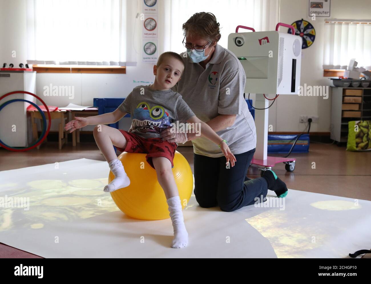 Callum McMichael alongside Paediatric Physiotherapist Kath Brimlow as he takes part in 1:1 session supporting development of posture and movement skills at the Craighalbert Centre. Coronavirus adaptations have been installed at the Scottish Centre for Children with Motor Impairments, Craighalbert Centre, Cumbernauld, as Scotland continues gradually lifting coronavirus lockdown measures. Stock Photo