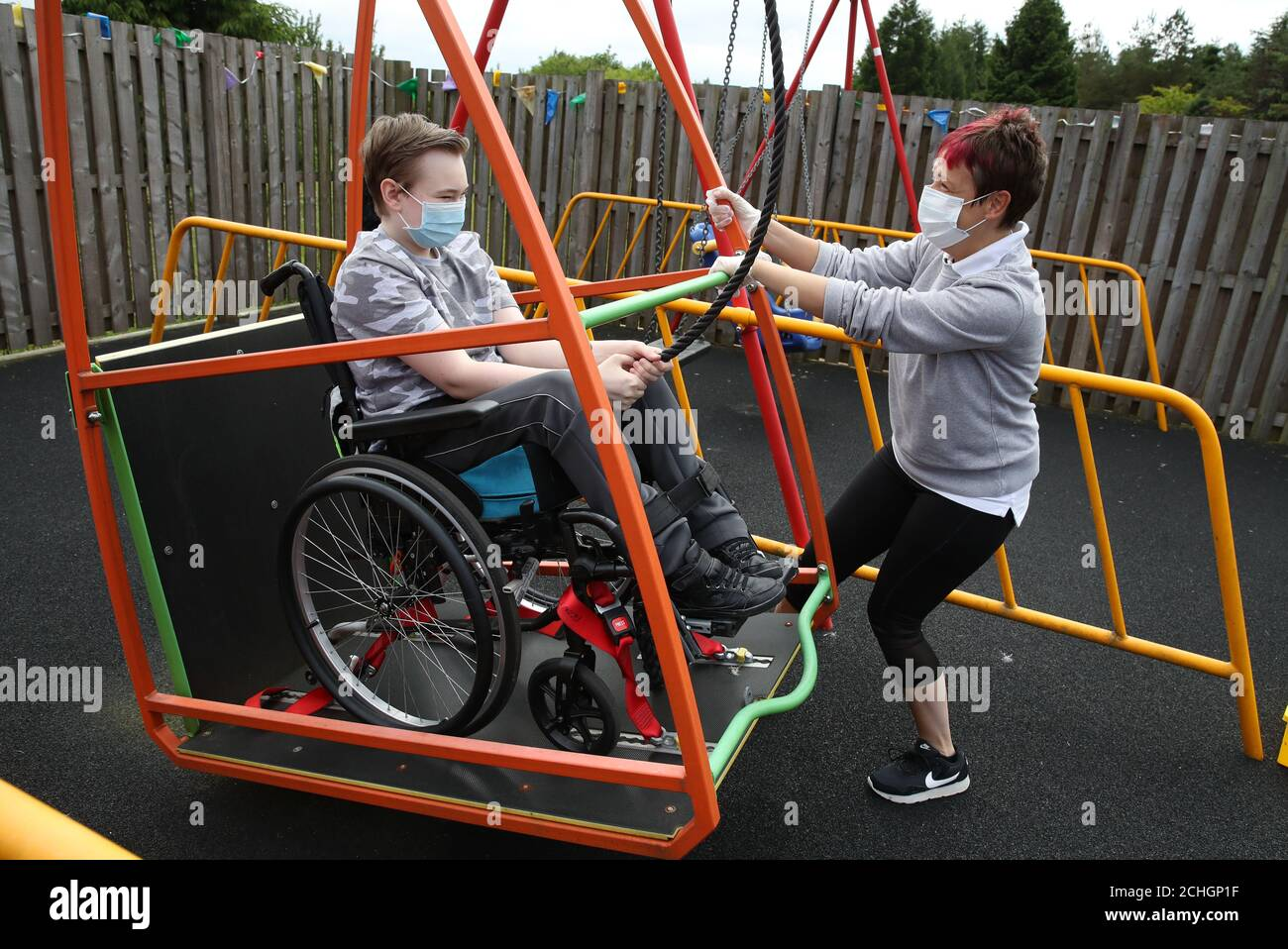 Embargoed to 0001 Monday June 22 Gregor Marshall alongside Early Years Practitioner Catherine Anderson as Gregor has a ride on the wheelchair swing in the outside therapy area at the Craighalbert Centre. Coronavirus adaptations have been installed at the Scottish Centre for Children with Motor Impairments, Craighalbert Centre, Cumbernauld, as Scotland continues gradually lifting coronavirus lockdown measures. Stock Photo