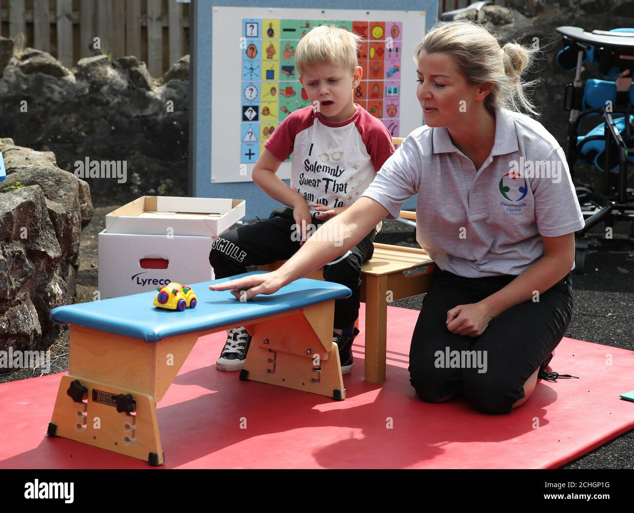 Embargoed to 0001 Monday June 22 Oliver Cunningham with Specialist Physiotherapist Leah Honohan use the weighing scales during a shared theraplay session in the outside therapy area at the Craighalbert Centre. These sessions are taking place to deliver blended learning to children who are shielding. Coronavirus adaptations have been installed at the Scottish Centre for Children with Motor Impairments, Craighalbert Centre, Cumbernauld, as Scotland continues gradually lifting coronavirus lockdown measures. Stock Photo
