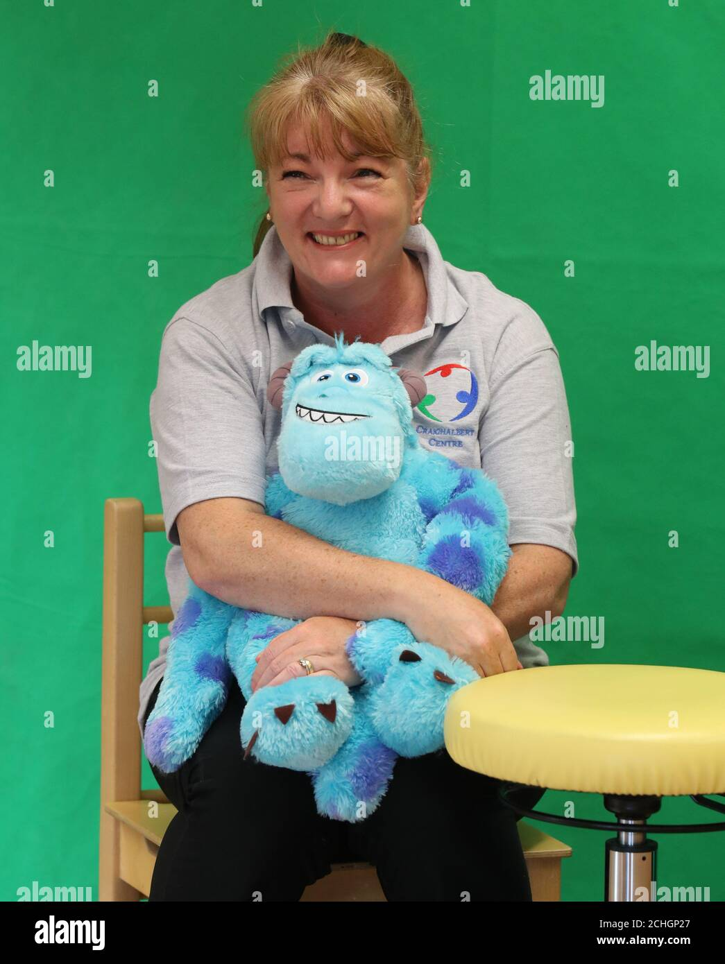Class teacher Margaret Poli holds centre mascot Sully as they take part in a story massage session via zoom at the Craighalbert Centre. These sessions are taking place to deliver blended learning to children who are shielding. Coronavirus adaptations have been installed at the Scottish Centre for Children with Motor Impairments, Craighalbert Centre, Cumbernauld, as Scotland continues gradually lifting coronavirus lockdown measures. Stock Photo