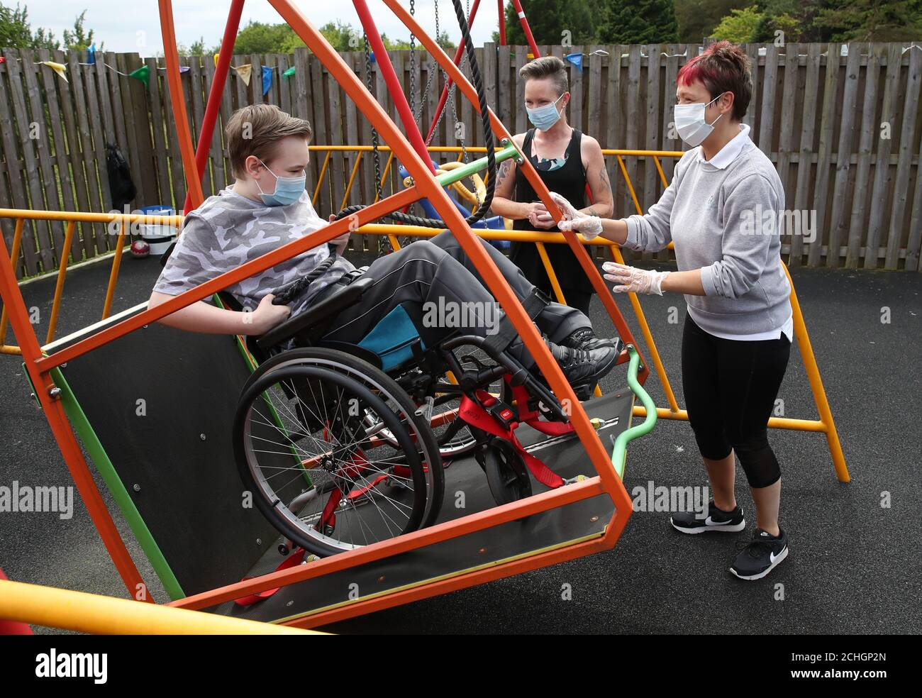 Embargoed to 0001 Monday June 22 Gregor Marshall with his mum Karen alongside Early Years Practitioner Catherine Anderson (right) as Gregor has a ride on the wheelchair swing in the outside therapy area at the Craighalbert Centre. Coronavirus adaptations have been installed at the Scottish Centre for Children with Motor Impairments, Craighalbert Centre, Cumbernauld, as Scotland continues gradually lifting coronavirus lockdown measures. Stock Photo