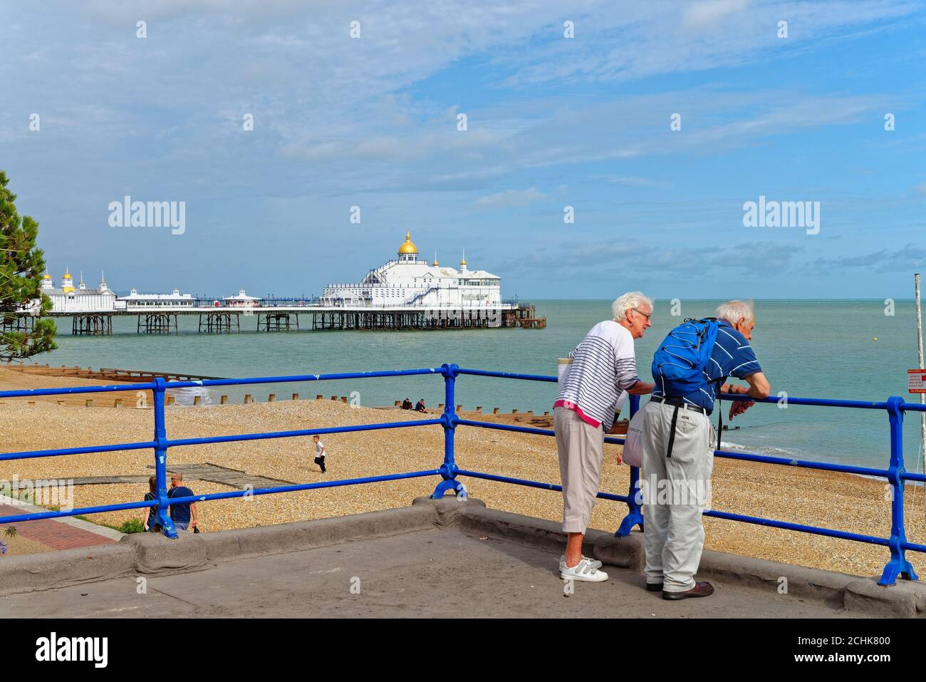 An elderly couple looking at the view from Eastbourne seafront with the pier in the background on a summers evening, East Sussex England UK Stock Photo
