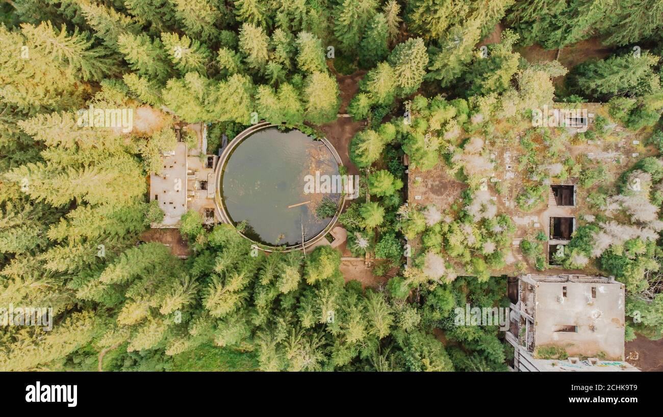 Top aerial view of abandoned water reservoir,tank, and buildings of old tin mine in Rolava,Ore mountains,Czech Republic. Beautiful nature from above. Stock Photo