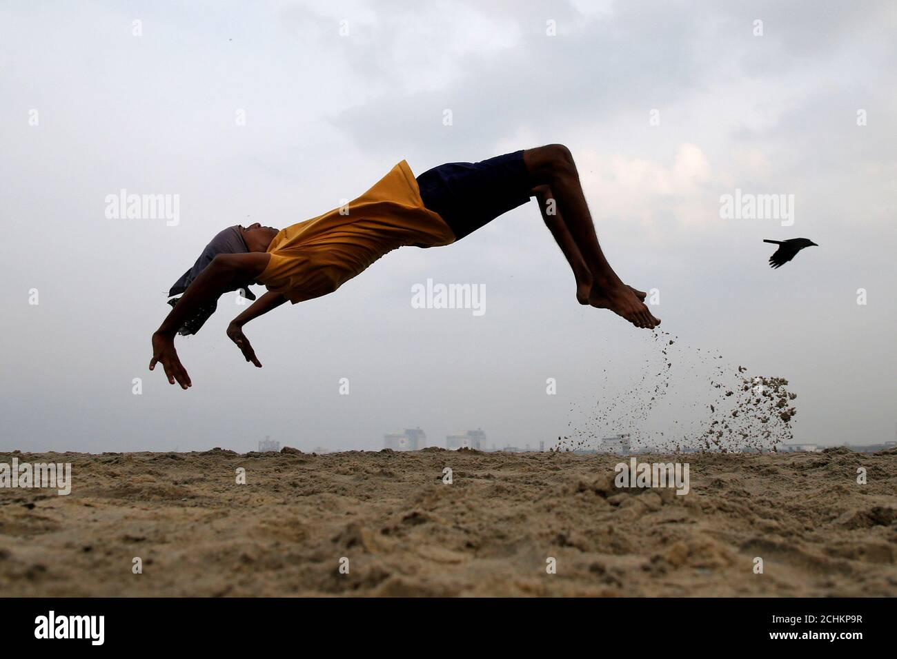 A boy practices somersaulting as he exercises at a beach in Kochi, India, March 11, 2019. REUTERS/Sivaram V     TPX IMAGES OF THE DAY Stock Photo