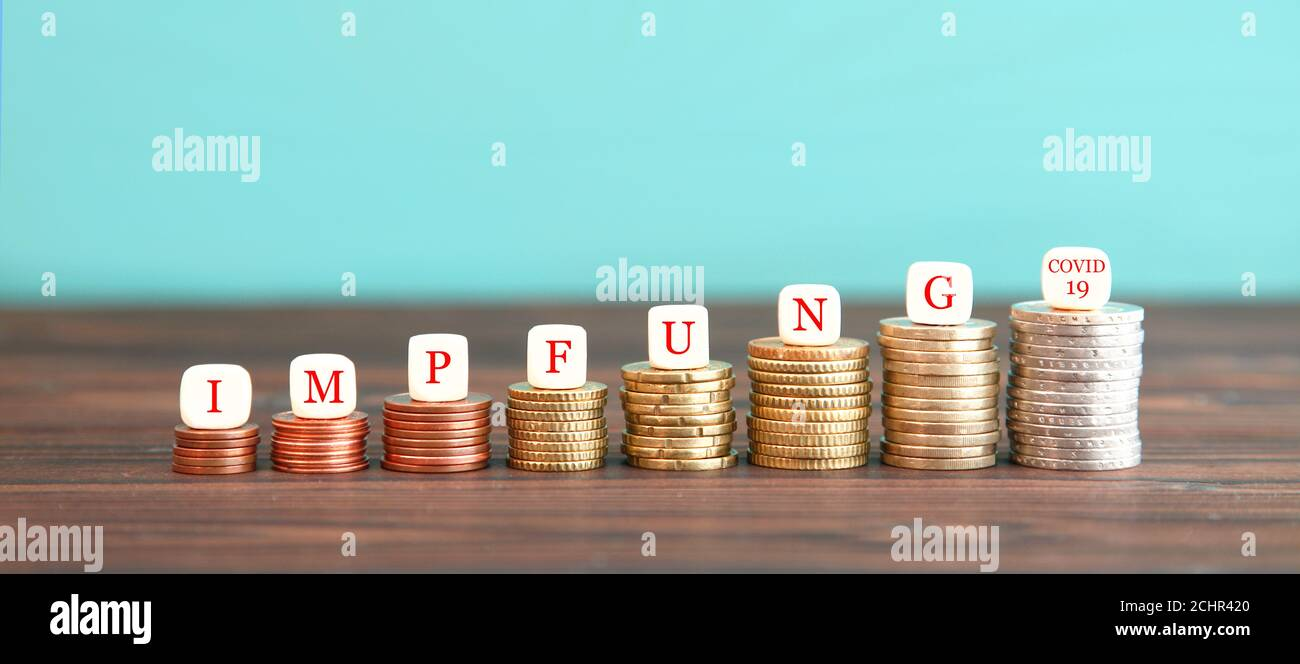 expenses due to the corona pandemic. dice form german expression Impfung COVID-19 (Vaccination COVID-19) increasing high stack of coins . rising costs Stock Photo