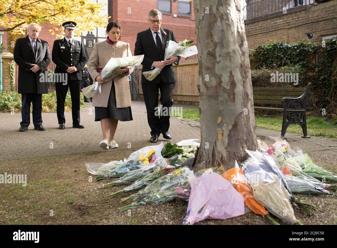 Prime Minister Boris Johnson stands with the Chief Constable of Essex Police, Ben-Julian Harrington, as Home Secretary Priti Patel lays flowers during a visit to Thurrock Council Offices in Grays, Britain, October 28, 2019. Stefan Rousseau/Pool via REUTERS Stock Photo