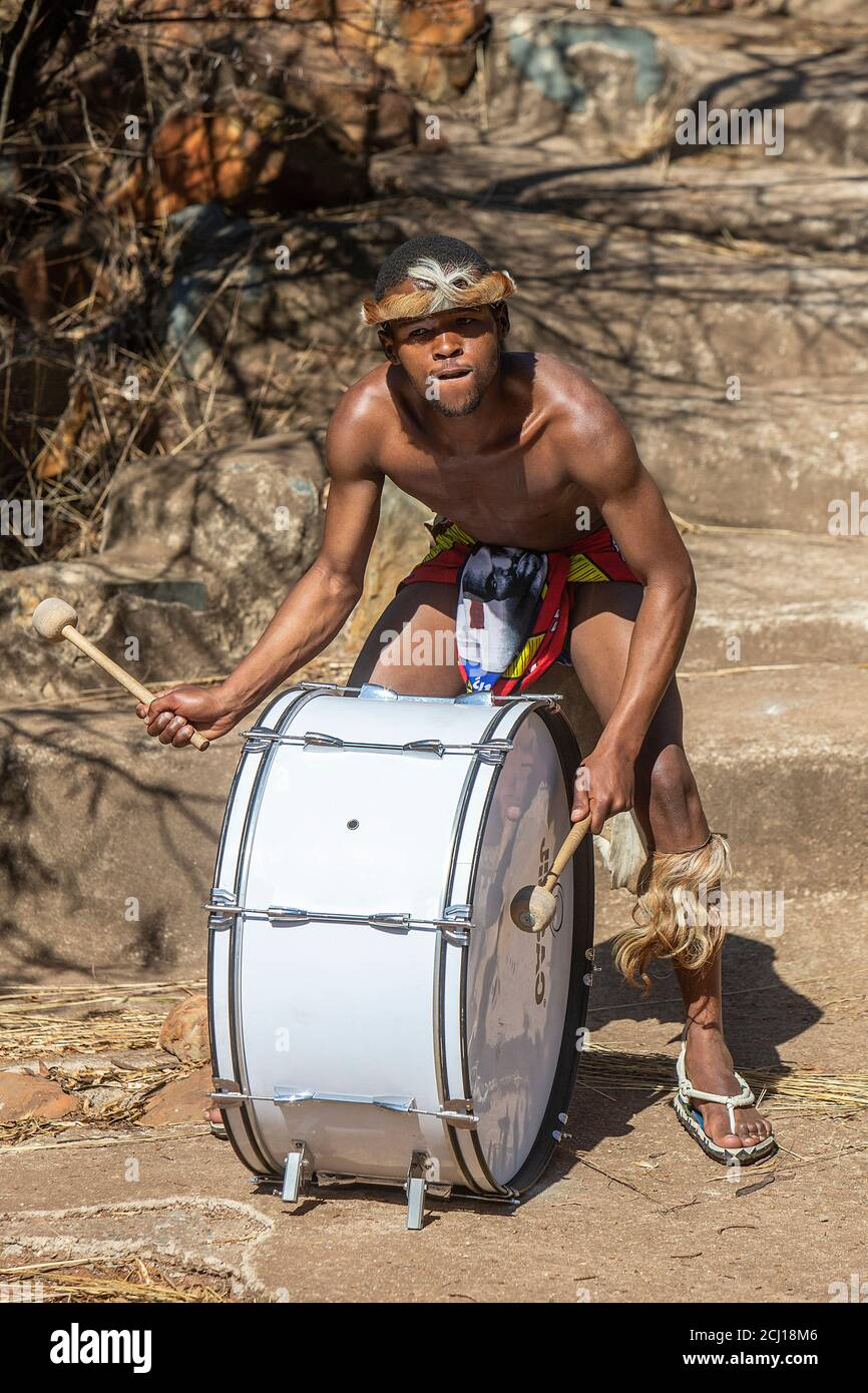 Zulu man in traditional dress playing the drum Stock Photo