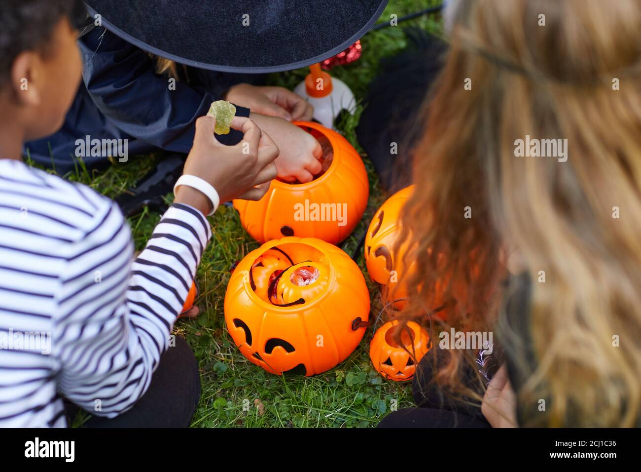 High angle view at group of kids wearing costumes taking candy from Halloween buckets outdoors, copy space Stock Photo