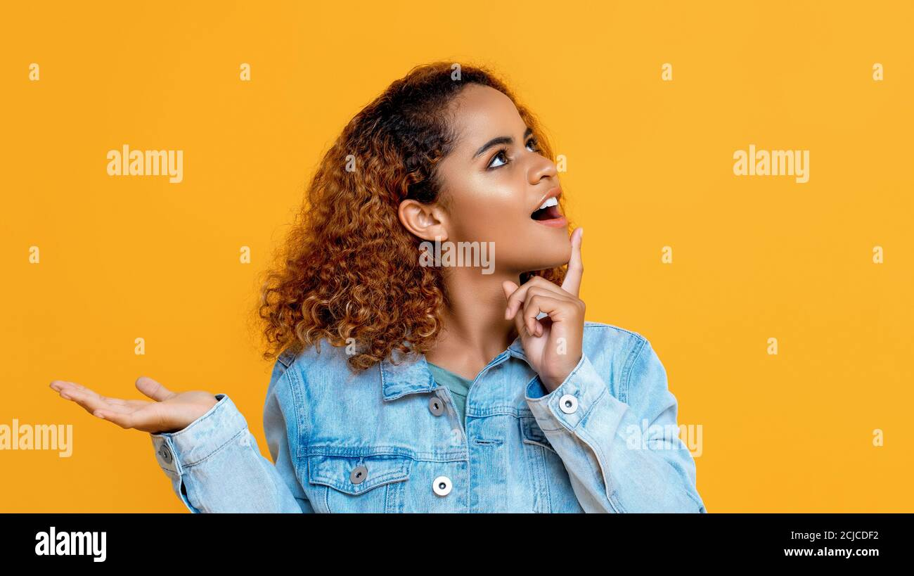 Side view portrait of thinking young African American woman looking up doing open palm gesture in isolated studio yellow background Stock Photo
