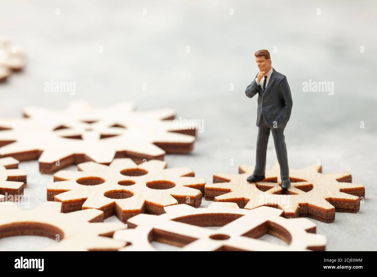 Business Analysis. Audit of the company. A businessman in a suit stands on gears as a symbol of business processes in the company. Stock Photo