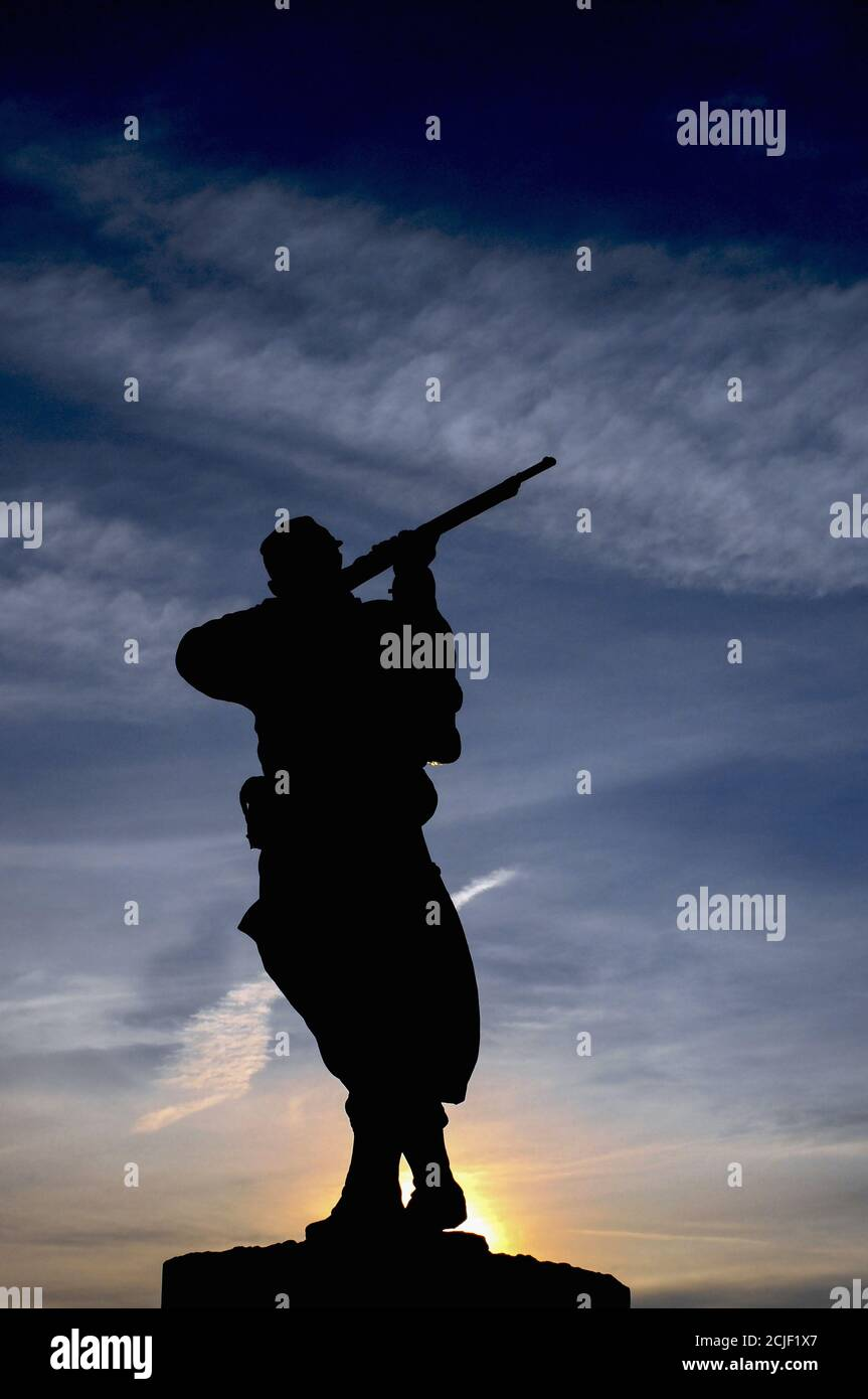 Bronze statue of a French rifleman or poilu silhouetted against the rising sun on the town monument at Monpazier in the Dordogne, Nouvelle-Aquitaine, France, to those who fell in the Franco-Prussian War of 1870-71. Stock Photo