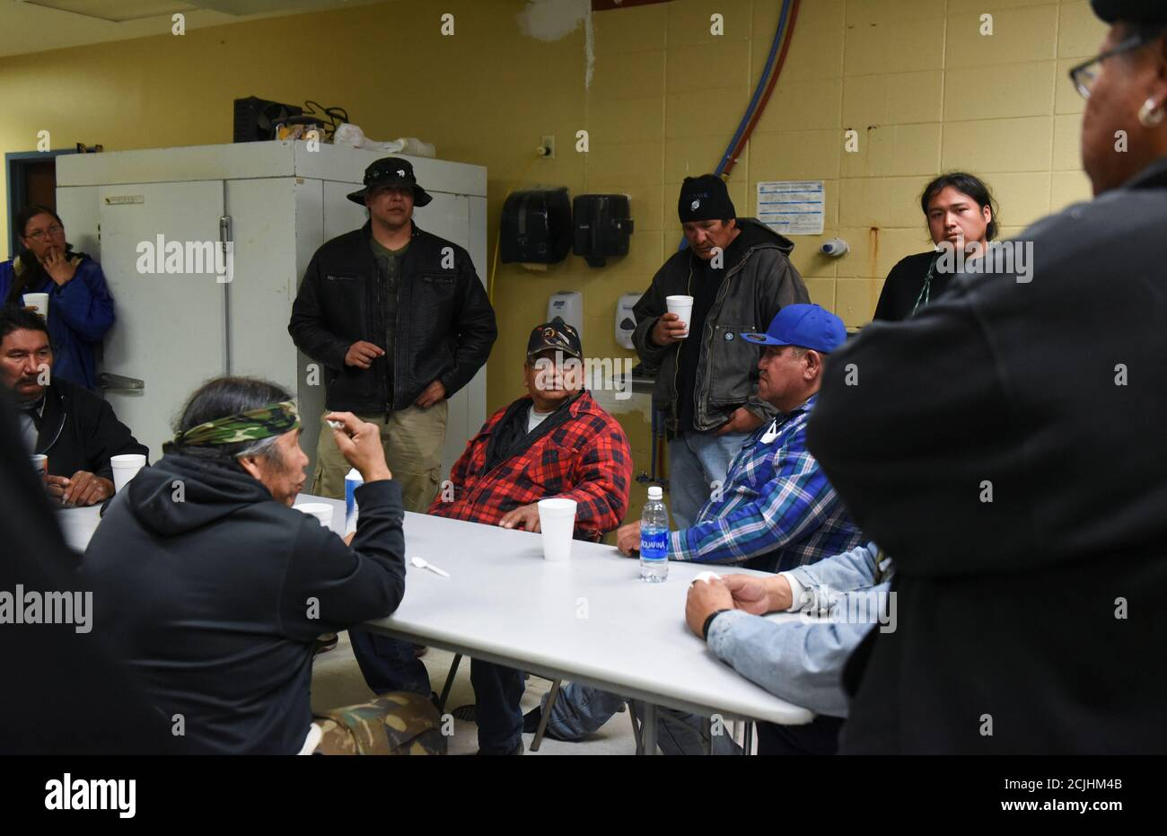 "Ivan Lookinghorse (C) and other Fort Laramie treaty riders meet in the kitchen of the Rockyford School gymnasium on the Pine Ridge Reservation in Rockyford, South Dakota, U.S., April 20, 2018. ""Understand that we, as a people, we have been in poverty, we have been in depression, we have been Christianised, we have been boarding schooled, our language has been taken away from us, but we are on our way back to who we once were,"" Lookinghorse said. ""We are standing up on our two feet,"" he continued ""We are taking our place in the world, the protectors of the Grandmother Earth."" REUTERS/Stephanie  Stock Photo"