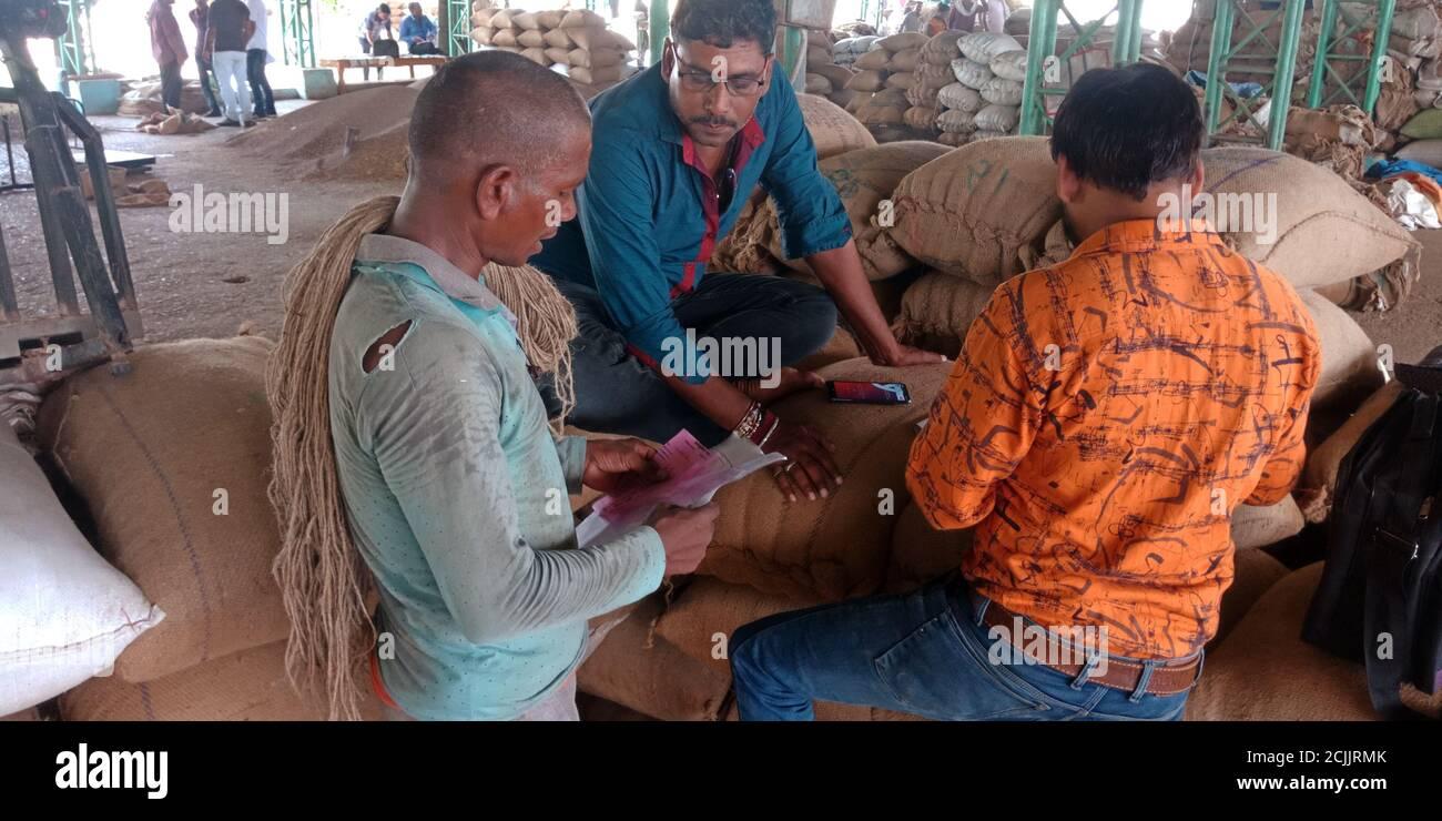 DISTRICT KATNI, INDIA - SEPTEMBER 18, 2019: Three Indian poor people seating around wheat grain sack at food corporation of indian galla mandi. Stock Photo