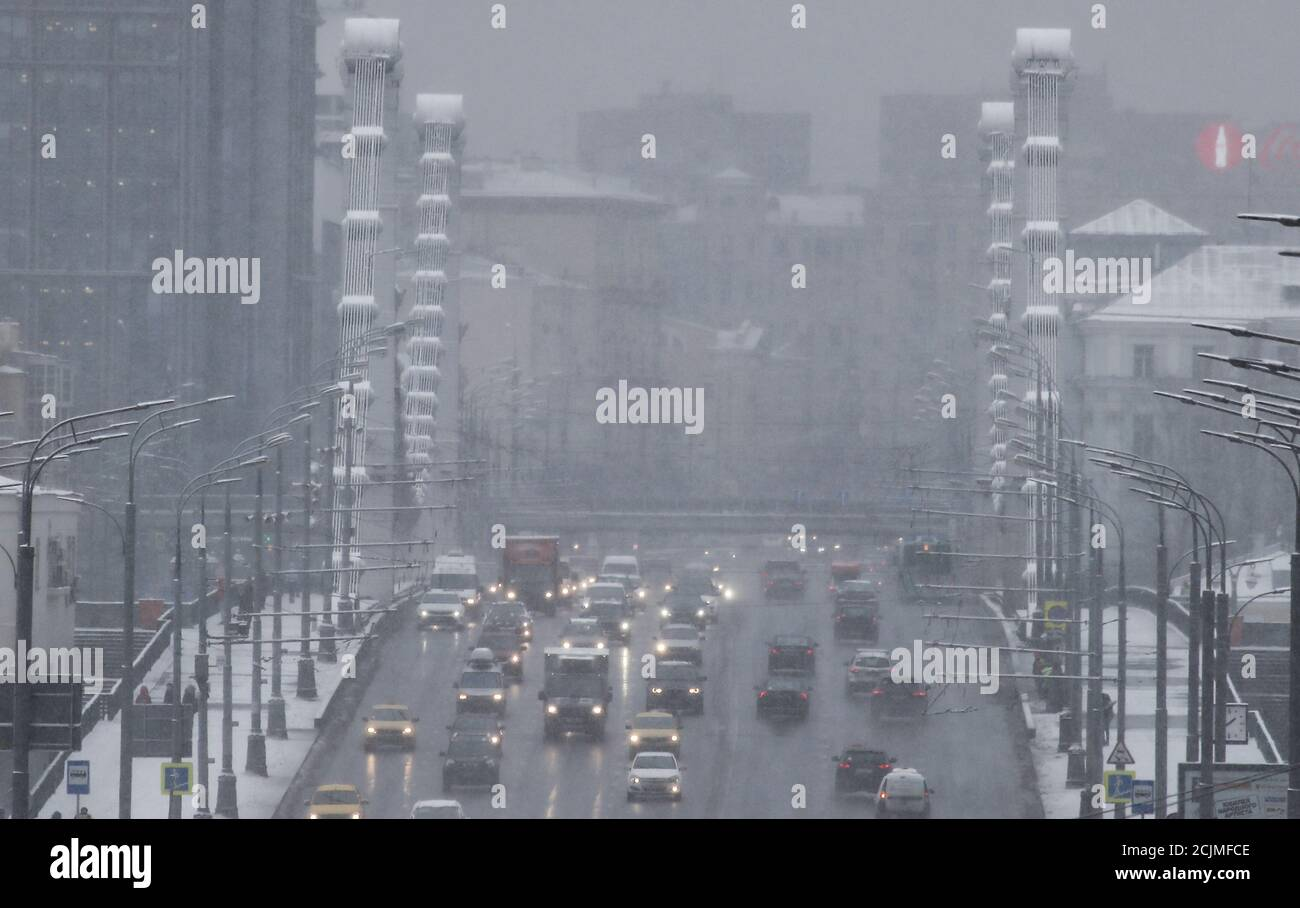 Vehicles drive along a road during snowfall in Moscow, Russia January 11, 2018. REUTERS/Maxim Shemetov Stock Photo