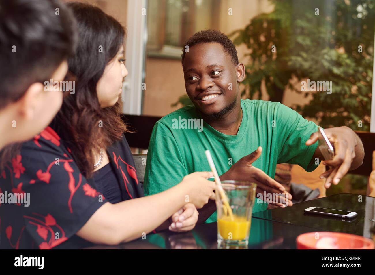 Multiracial group of friends having a coffee together. A young black man explains something to his girlfriend surrounded by friends. Stock Photo