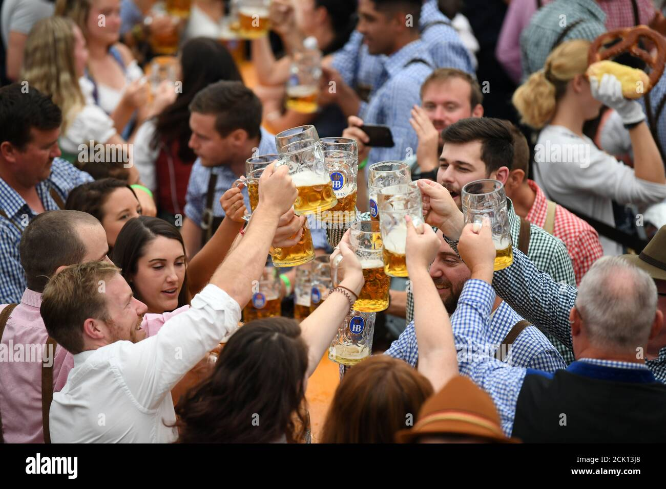 Visitors cheer with beers in a tent during Oktoberfest in Munich, Germany, September 22, 2019. REUTERS/Andreas Gebert Stock Photo