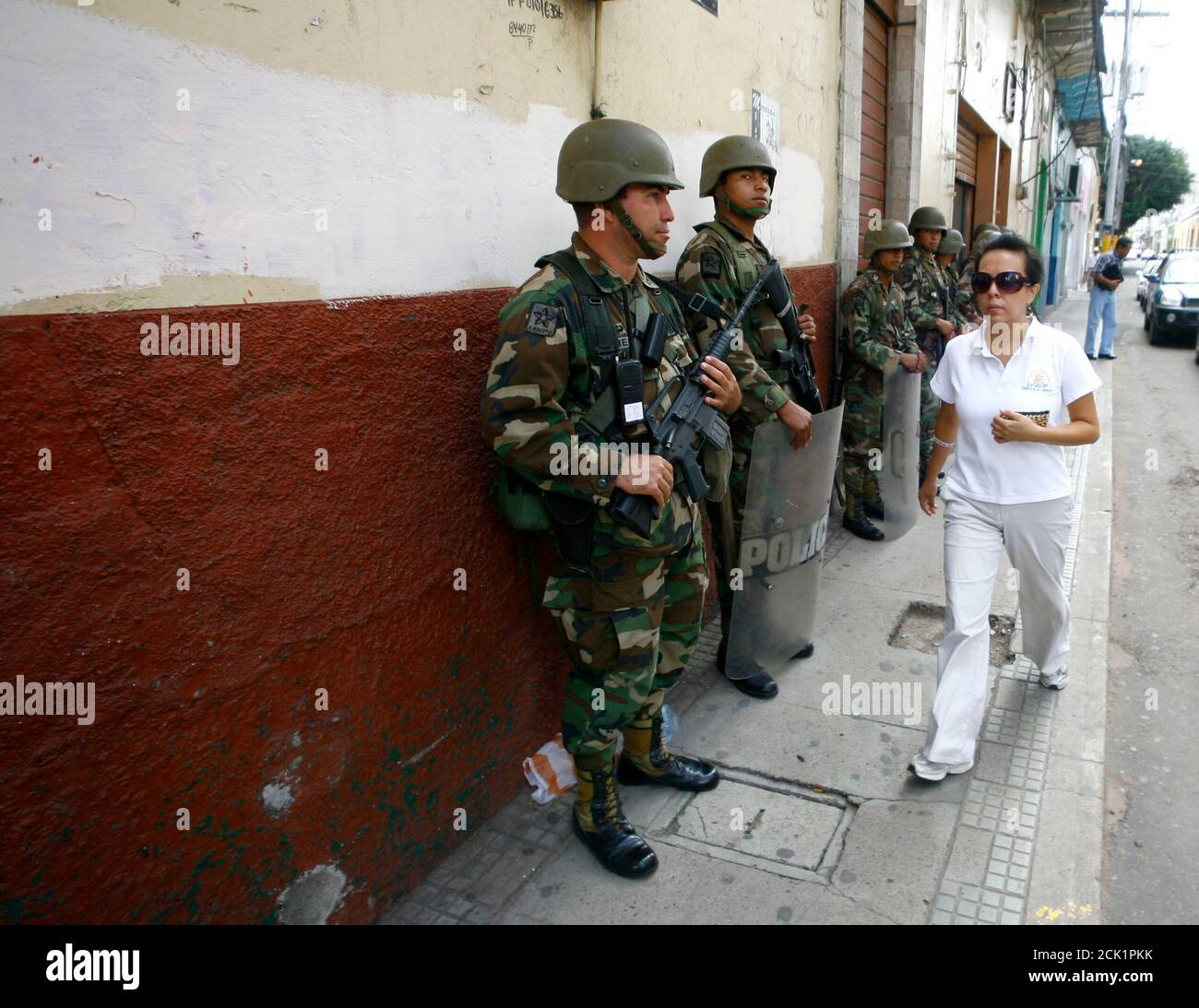 A woman walks past soldiers standing guard in Tegucigalpa July 7, 2009. Ousted Honduran President Manuel Zelaya said on Tuesday he accepted the mediation of Costa Rican President Oscar Arias to try to solve his country's political crisis following the June 28 coup that ousted him. REUTERS/Henry Romero (HONDURAS CONFLICT MILITARY POLITICS) Stock Photo