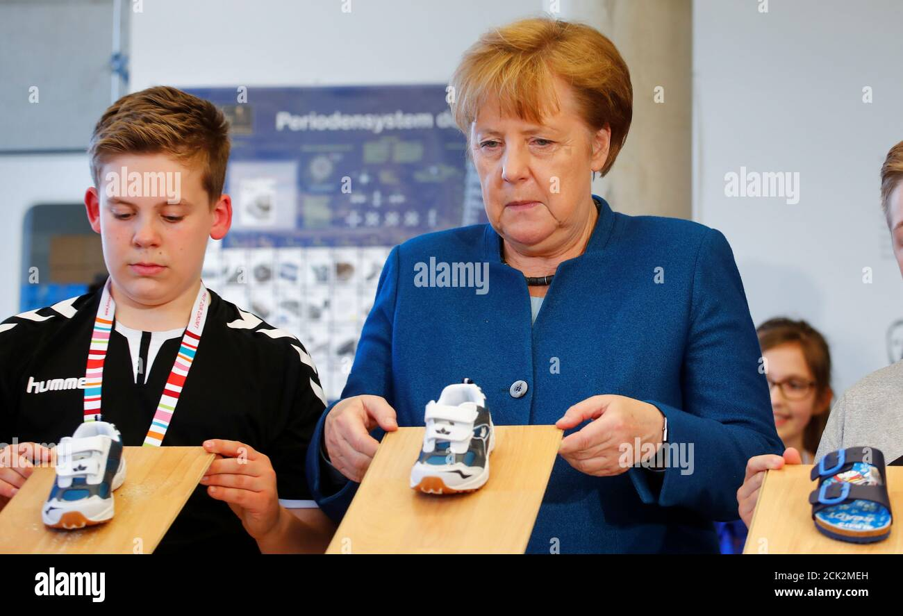 German Chancellor Angela Merkel And A Young Student Test The Grip Of Sport Shoes During Merkel S Visit To The Junior University In Wuppertal Germany May 13 2019 Reuters Wolfgang Rattay Stock Photo Alamy