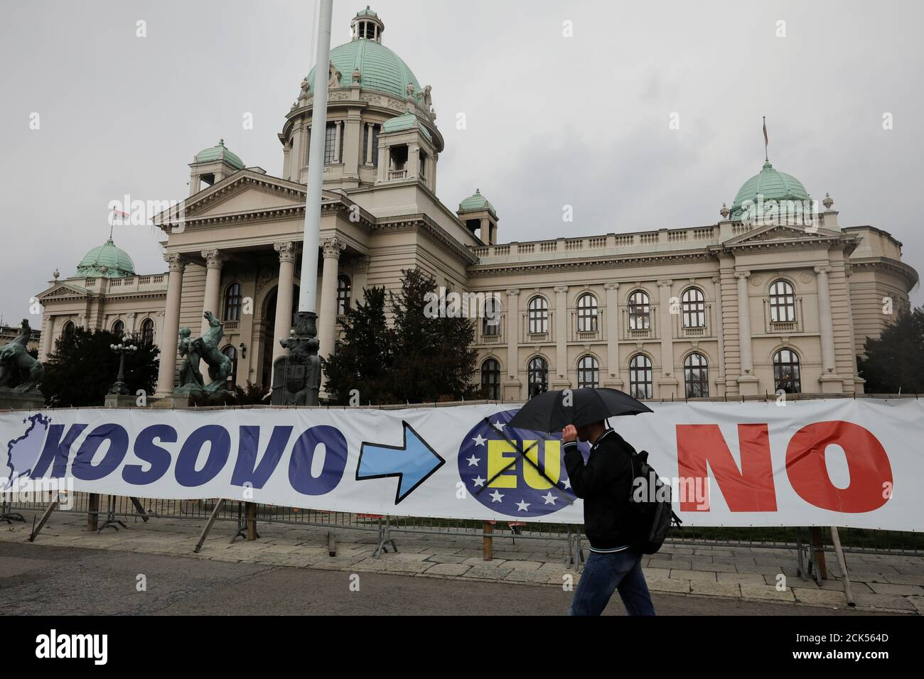 A man walks past a banner in front of Serbian parliament building in central Belgrade, Serbia, March 27, 2018. REUTERS/Marko Djurica Stock Photo