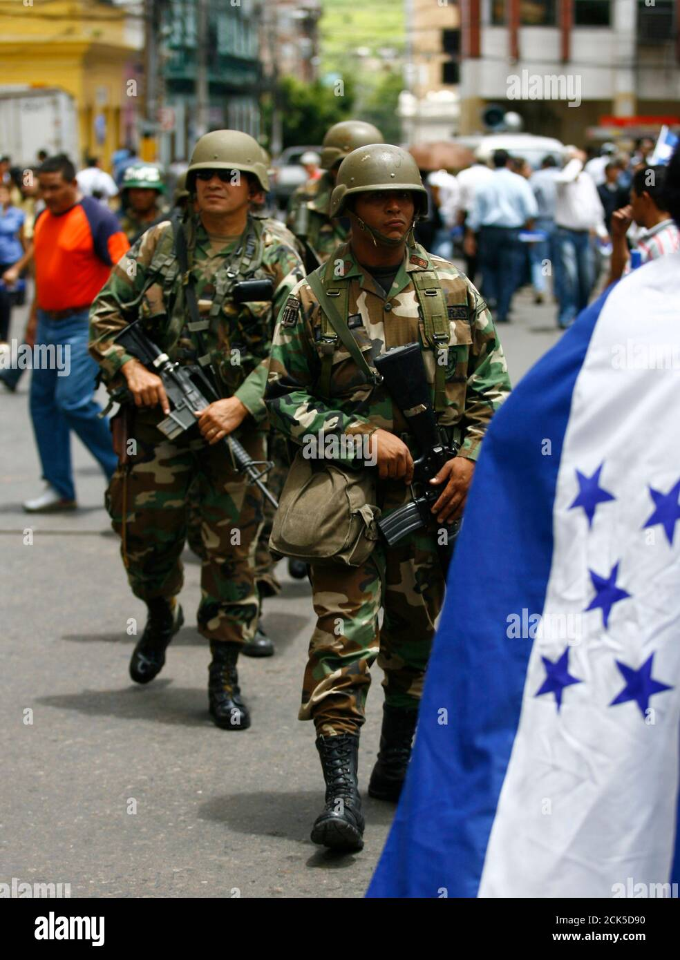 Soldiers on guard walk past supporters of Honduras' interim President Roberto Micheletti during a march in Tegucigalpa July 7, 2009. Ousted Honduran President Manuel Zelaya said on Tuesday he accepted the mediation of Costa Rican President Oscar Arias to try to solve his country's political crisis following the June 28 coup that ousted him. REUTERS/Henry Romero (HONDURAS POLITICS CONFLICT MILITARY) Stock Photo