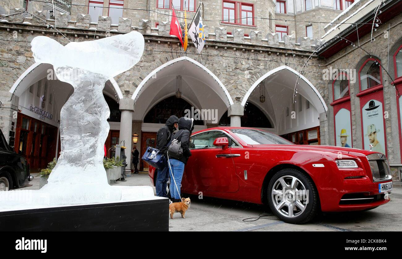 """Ice sculpture of the """"Spirit of Ecstasy"""", the bonnet ornament of Rolls-Royce cars, also known as """"Emily"""", stands in front of a Rolls-Royce Wraith car in the mountain resort of St. Moritz, Switzerland February 2, 2017. REUTERS/Arnd Wiegmann Stock Photo"""