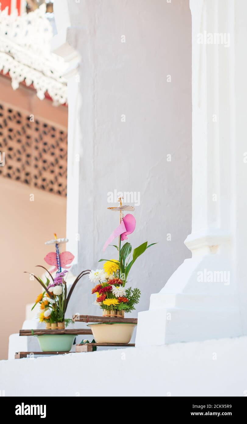 Traditional flowers offerings to buddha at ancient pagoda, the belief is that the offering appeases the spirits, leading to merit and enlightenment. Stock Photo