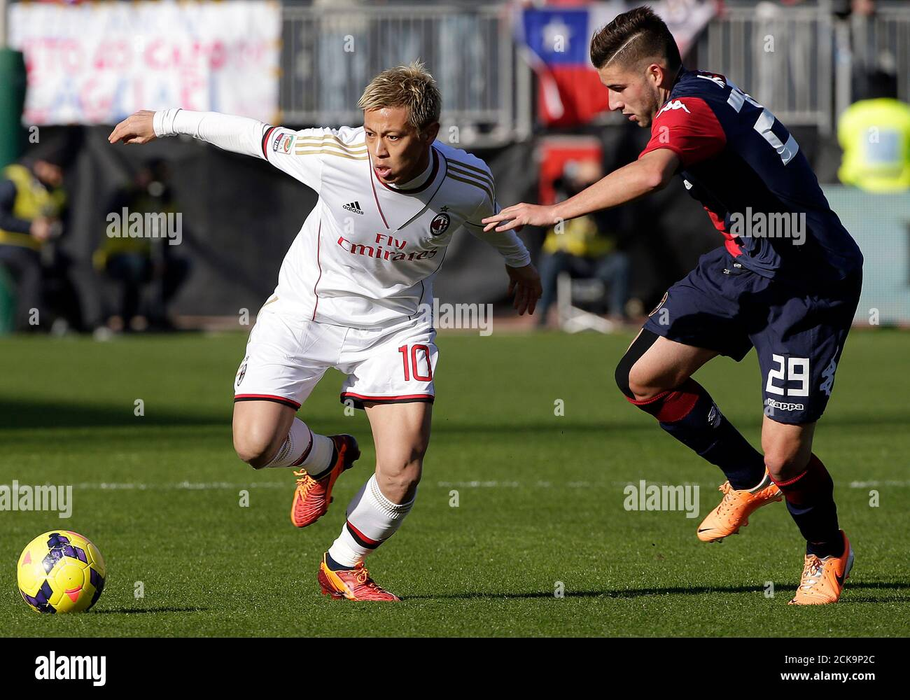 AC Milan's Keisuke Honda (L) challenges Nicola Murru of Cagliari during their Italian Serie A soccer match at the Sant'Elia stadium in Cagliari January 26, 2014.  REUTERS/Max Rossi (ITALY - Tags: SPORT SOCCER) Stock Photo
